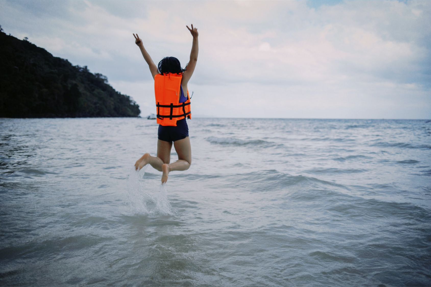 Girl in a life jacket jumping into a lake