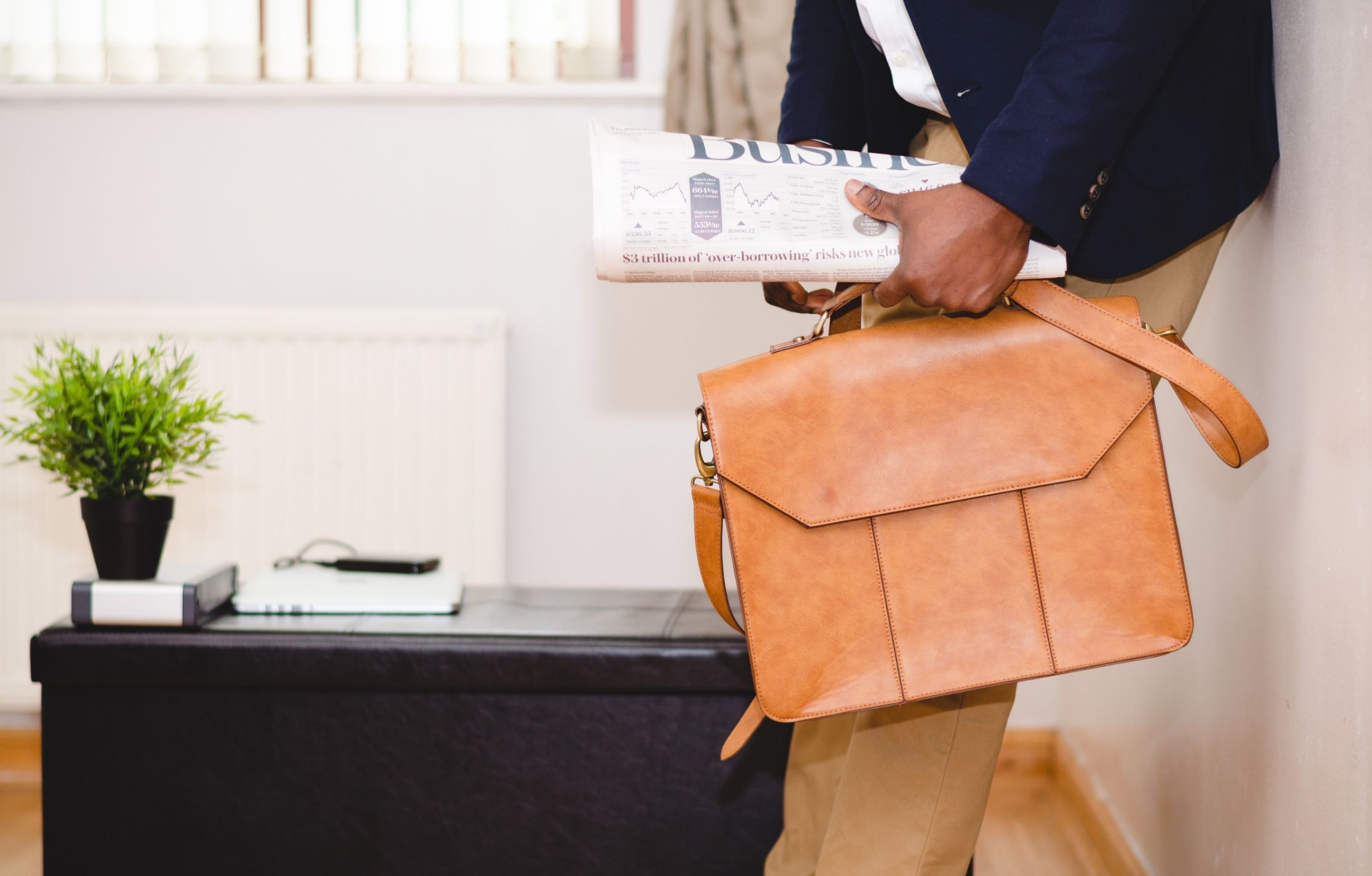 Man holding a business newspaper and a briefcase