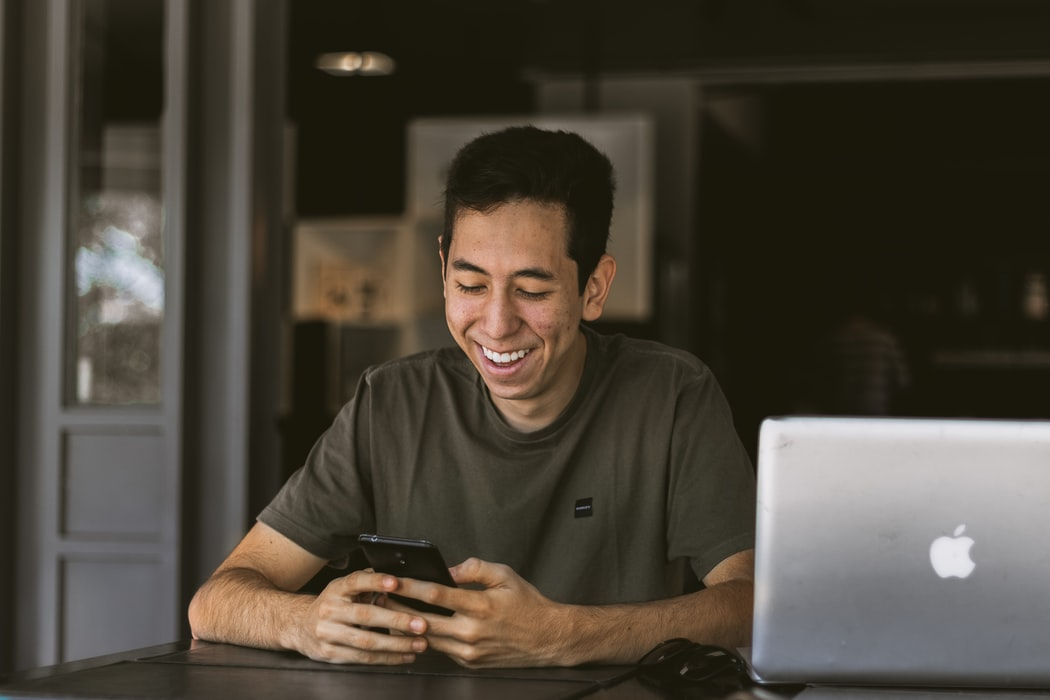 Man looking at phone and smiling