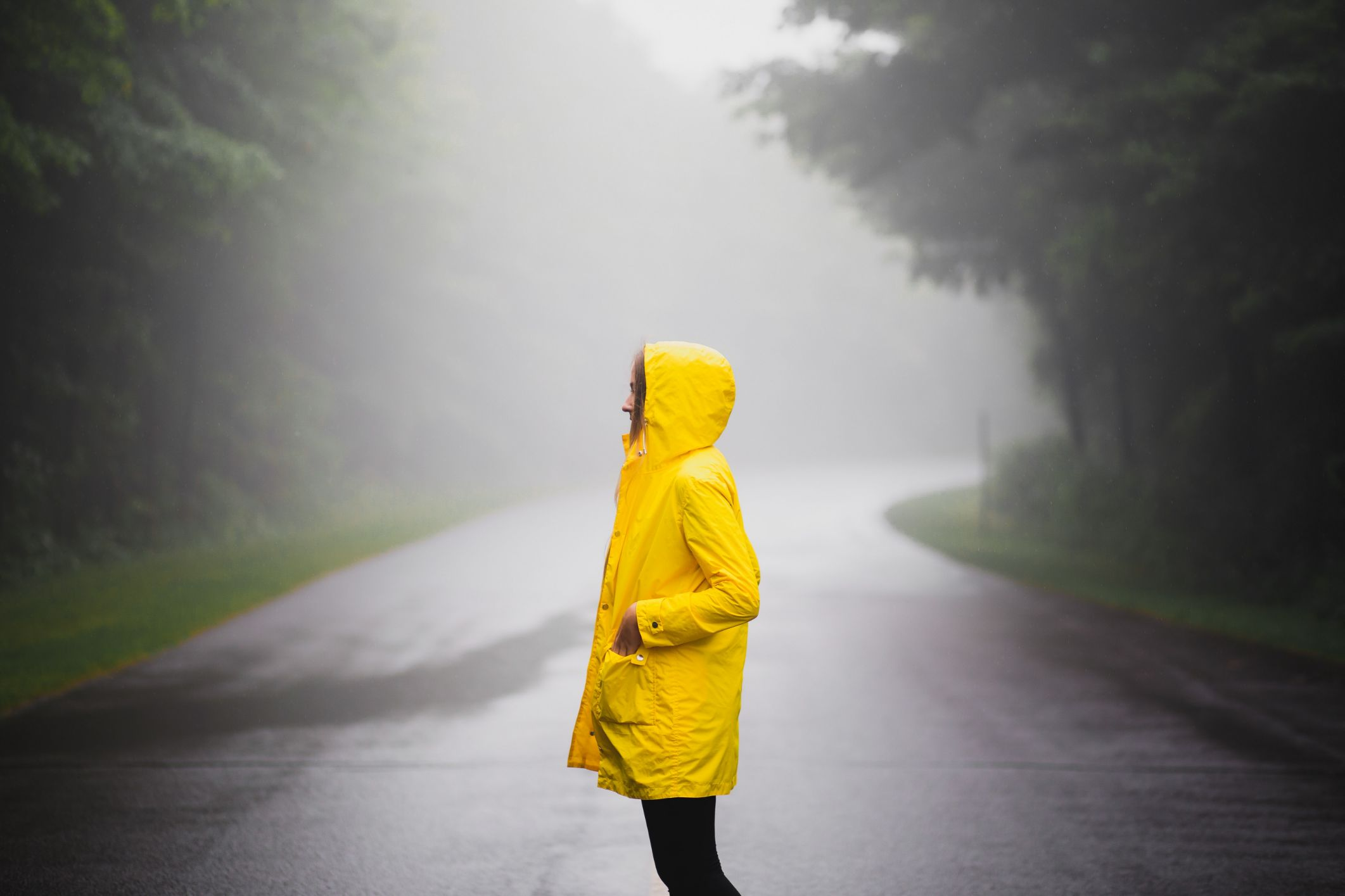 woman standing on a road in a raincoat