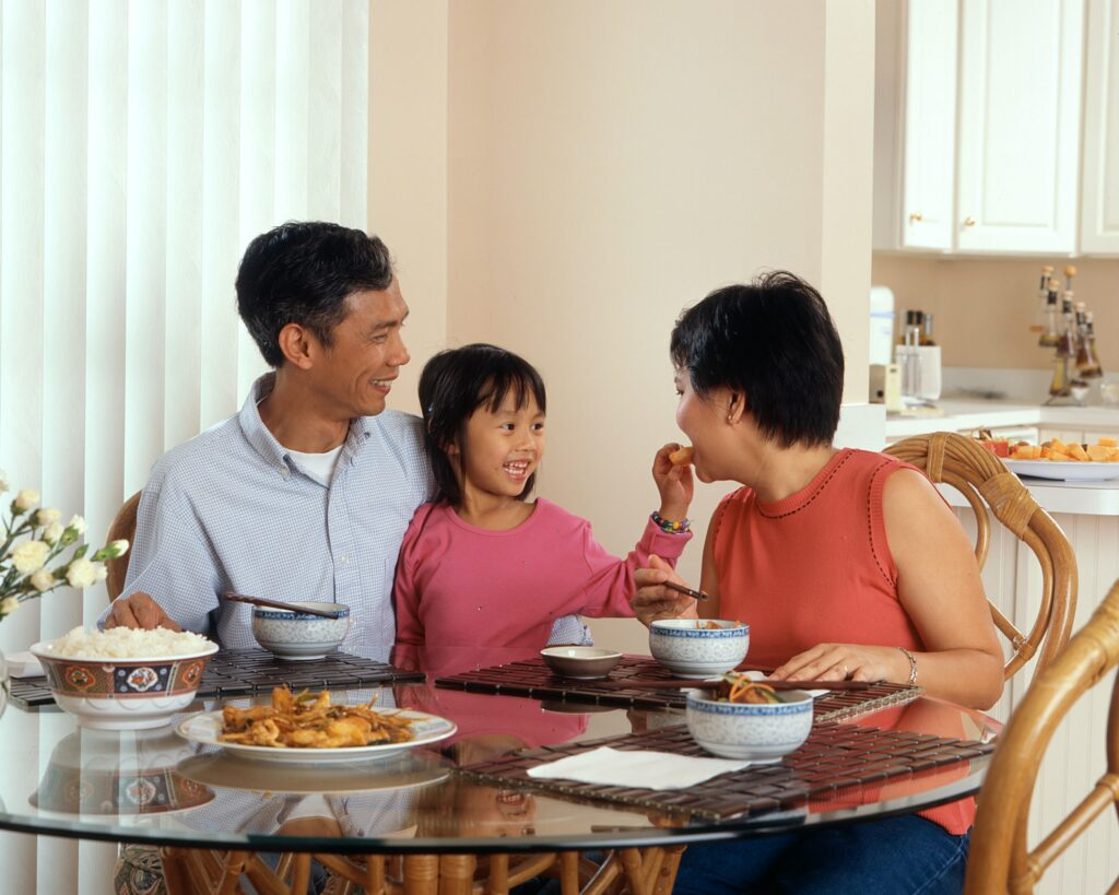 Family with a young child sitting at dinner table together