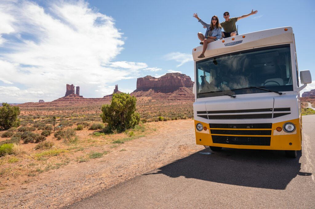 couple sitting on RV at park with buttes