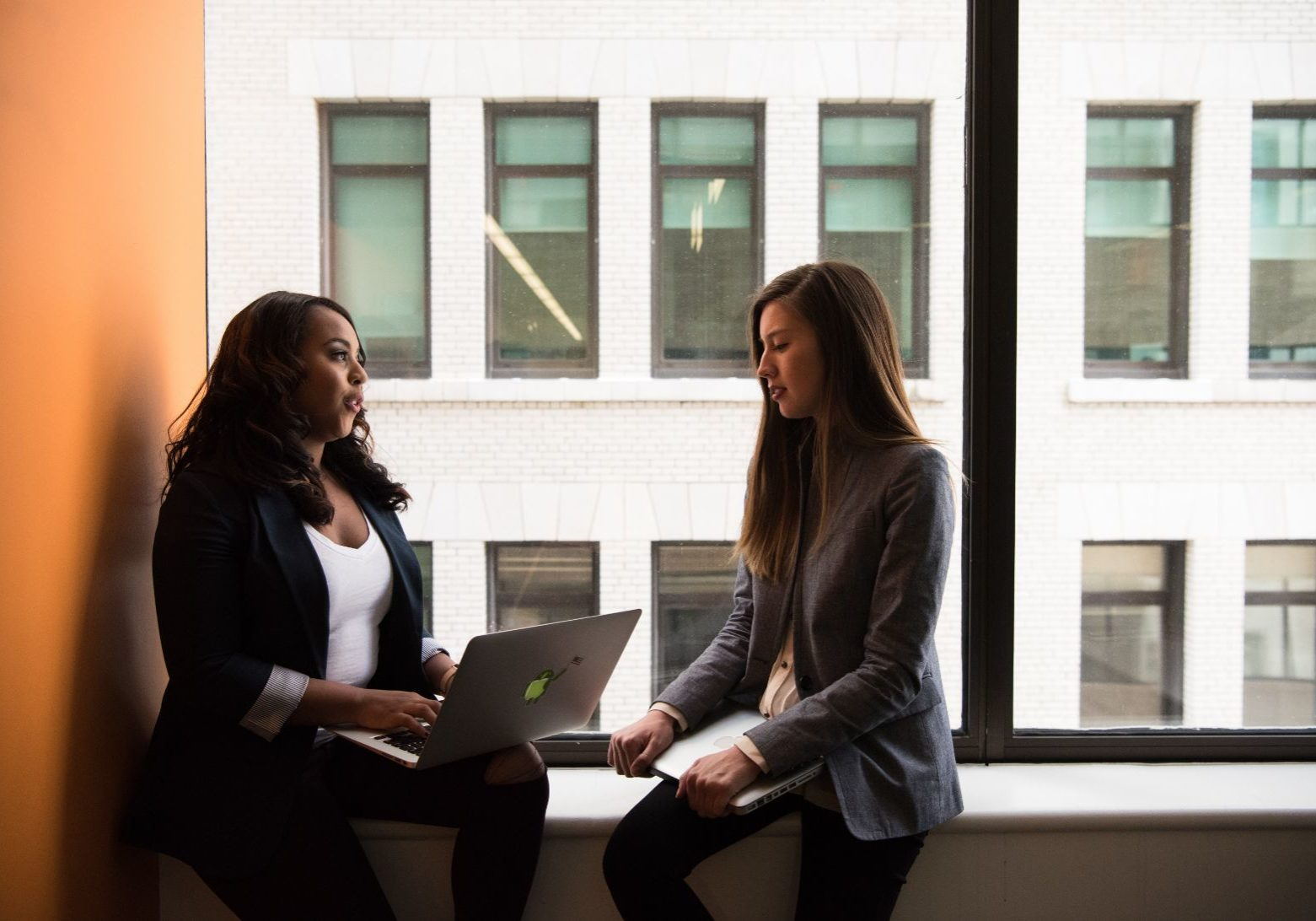 two women sitting on a windowsill having a business meeting